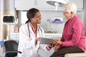 Doctor discussing records with senior female patient SMALL